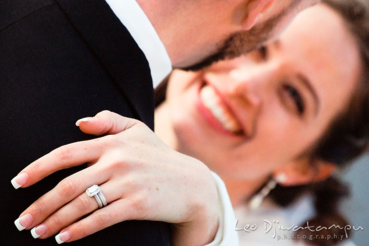 Bride smiling, looking at groom, showing wedding and engagement ring.