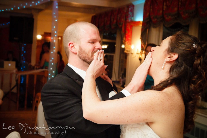Bride and groom shoving cake to each other's mouth. Kitty Knight House Georgetown Chestertown MD Wedding Photographer