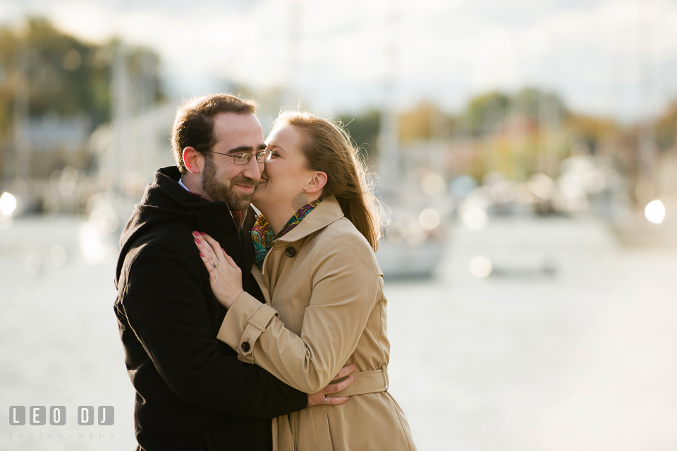Engaged girl laughing and kissing her fiancé by the boat dock. Annapolis Eastern Shore Maryland pre-wedding engagement photo session at downtown, by wedding photographers of Leo Dj Photography. http://leodjphoto.com