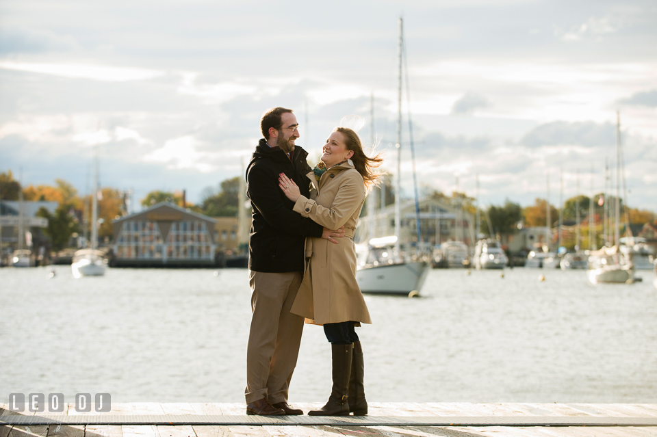Engaged couple smiling and hugging on the pier. Annapolis Eastern Shore Maryland pre-wedding engagement photo session at downtown, by wedding photographers of Leo Dj Photography. http://leodjphoto.com