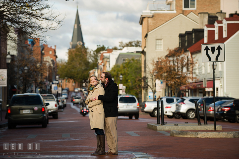 Engaged man cuddling his fiancée on the Main Street with the church circle in the background. Annapolis Eastern Shore Maryland pre-wedding engagement photo session at downtown, by wedding photographers of Leo Dj Photography. http://leodjphoto.com