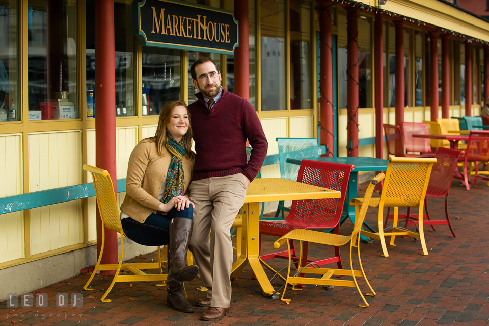 Engaged couple sitting by the tables outside Market House and enjoying the view of downtown dock. Annapolis Eastern Shore Maryland pre-wedding engagement photo session at downtown, by wedding photographers of Leo Dj Photography. http://leodjphoto.com