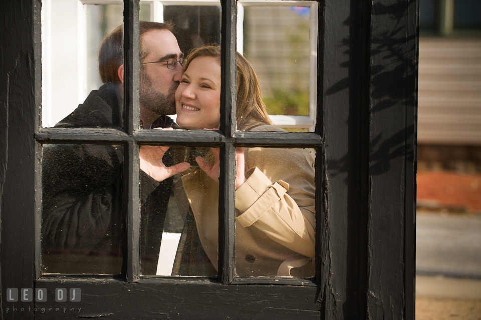 Engaged man kissing his fiance behind a glass door. Annapolis Eastern Shore Maryland pre-wedding engagement photo session at downtown, by wedding photographers of Leo Dj Photography. http://leodjphoto.com