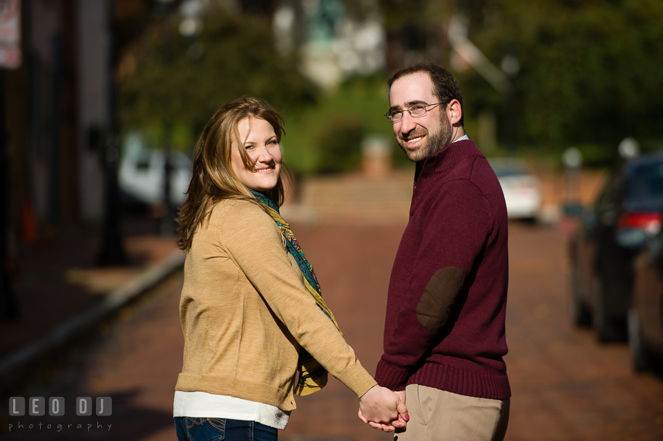 Engaged couple strolling along brick road and holding hands. Annapolis Eastern Shore Maryland pre-wedding engagement photo session at downtown, by wedding photographers of Leo Dj Photography. http://leodjphoto.com