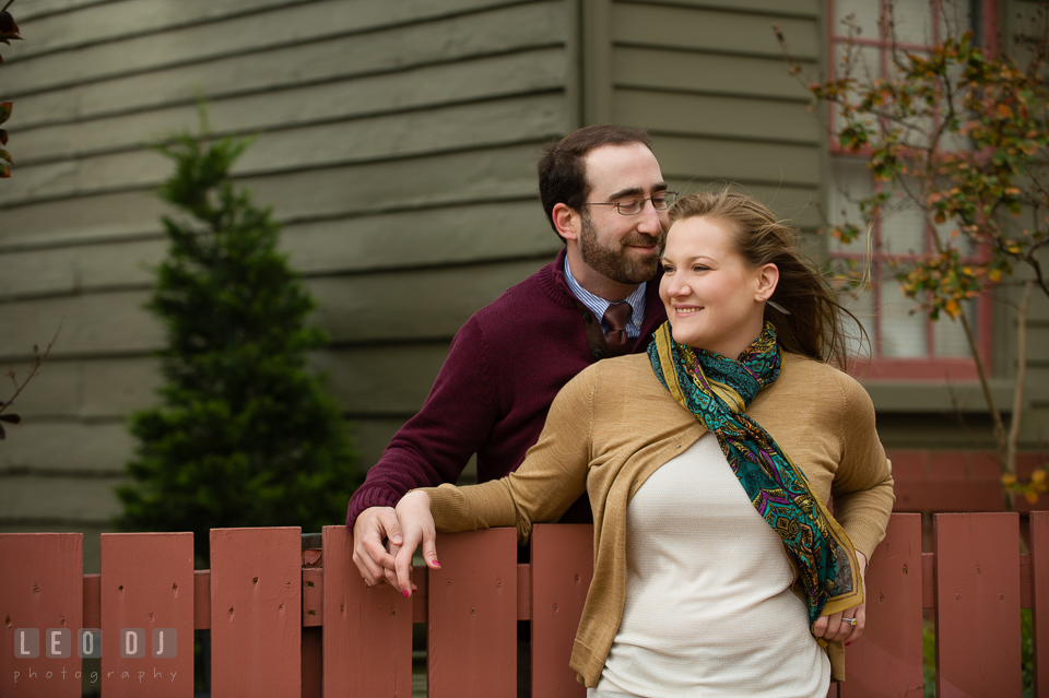 Engaged girl leaning over a wooden fence and cuddled by her fiance. Annapolis Eastern Shore Maryland pre-wedding engagement photo session at downtown, by wedding photographers of Leo Dj Photography. http://leodjphoto.com