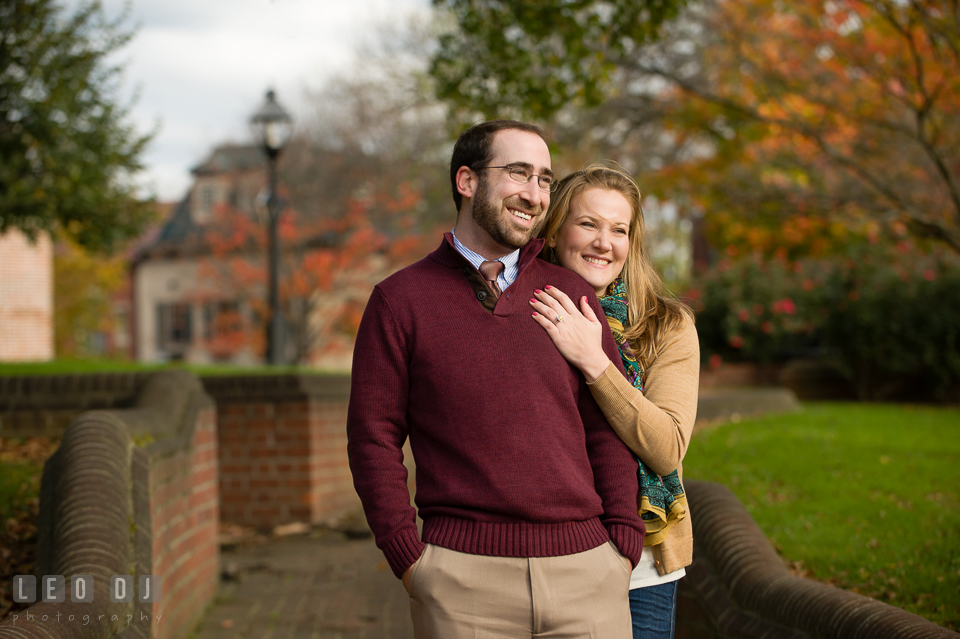 Engaged woman cuddled her fiance, smiling together by the State House. Annapolis Eastern Shore Maryland pre-wedding engagement photo session at downtown, by wedding photographers of Leo Dj Photography. http://leodjphoto.com