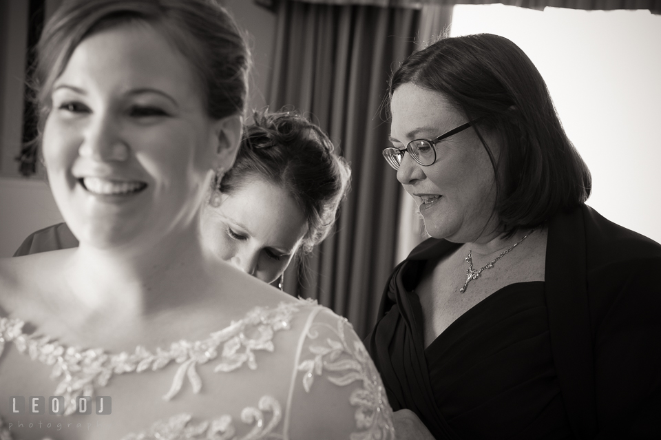 Mother and Matron of Honor helping Bride putting on the dress. The Tidewater Inn wedding, Easton, Eastern Shore, Maryland, by wedding photographers of Leo Dj Photography. http://leodjphoto.com