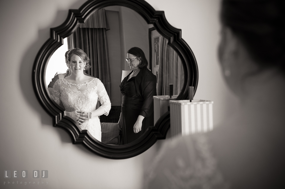 Bride looking at mirror while having her wedding gown put on. The Tidewater Inn wedding, Easton, Eastern Shore, Maryland, by wedding photographers of Leo Dj Photography. http://leodjphoto.com
