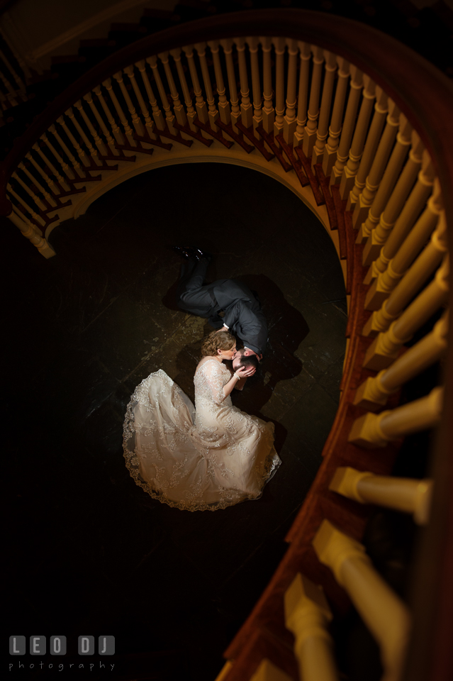 Bride and Groom lying on the floor kissing, framed by the circular stairway. The Tidewater Inn wedding, Easton, Eastern Shore, Maryland, by wedding photographers of Leo Dj Photography. http://leodjphoto.com