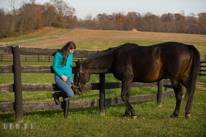 Girl and a horse by a fence on the field. Montgomery County high school senior portrait session at Wyndham Oaks, Boyds, Maryland horse stables by photographer Leo Dj Photography. http://leodjphoto.com