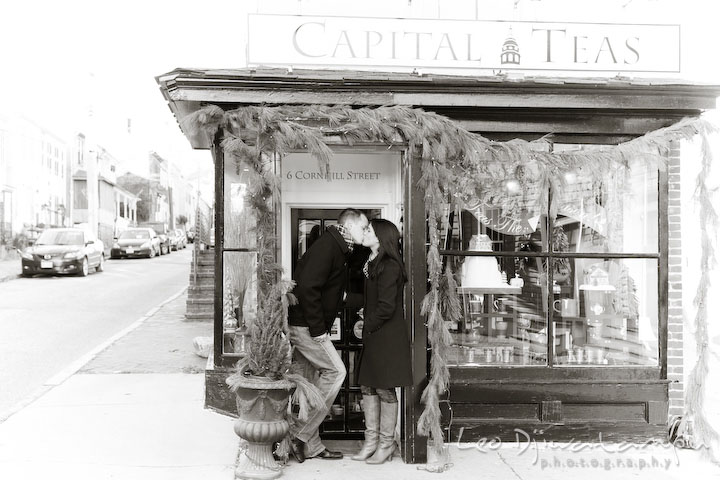 engaged couple kissing in front of a store. Urban City Pre-wedding Engagement Photographer Annapolis MD