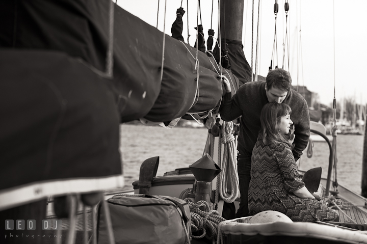 Engaged guy on a sailboat kissing his fiancée. Pre-wedding engagement photo session at Annapolis, Eastport, Maryland, Quiet Waters Park, by wedding photographers of Leo Dj Photography. http://leodjphoto.com