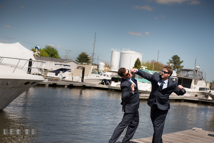 groom and best man pretending to fight at hilton garden inn boat dock kent island - Hilton Garden Inn Kent Island