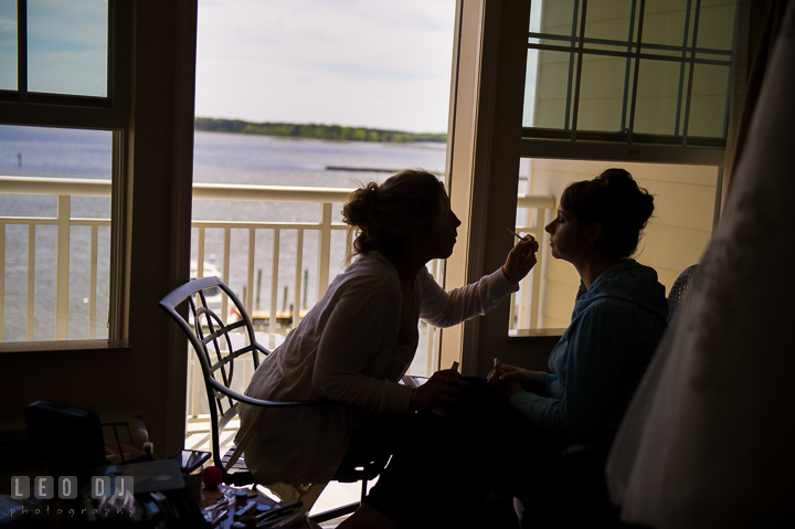 Silhouette of Bride getting make up done in hotel room of Hilton Garden Inn with beautiful waterfront view from balcony. Kent Island Maryland Matapeake Beach wedding ceremony and getting ready photo, by wedding photographers of Leo Dj Photography. http://leodjphoto.com