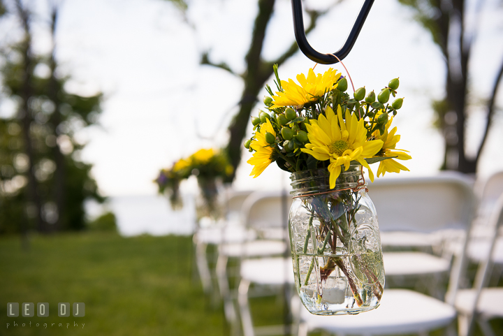 Yellow daisy flower on mason jar for decoration on isle for ceremony. Kent Island Maryland Matapeake Beach wedding ceremony and getting ready photo, by wedding photographers of Leo Dj Photography. http://leodjphoto.com