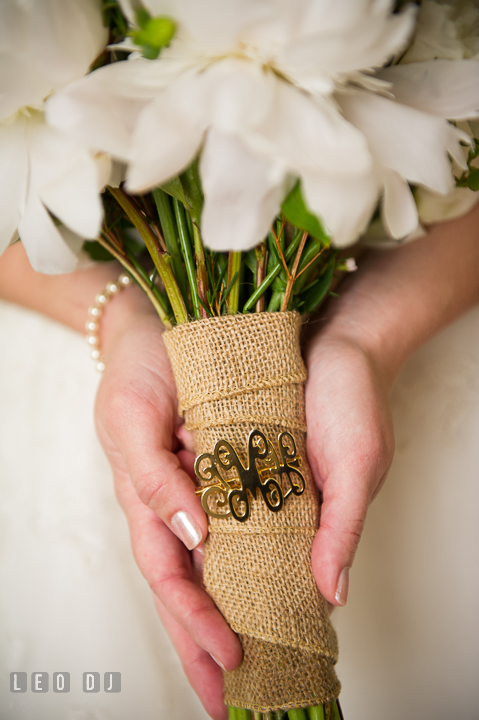 Bride holding her floral bouquet with heirloom pin from Grandmother on burlap. Kent Island Maryland Matapeake Beach wedding ceremony and getting ready photo, by wedding photographers of Leo Dj Photography. http://leodjphoto.com