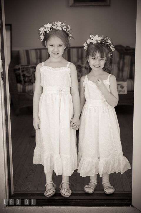 Two cute flower girls standing by a door holding hands. Kent Island Maryland Matapeake Beach wedding ceremony and getting ready photo, by wedding photographers of Leo Dj Photography. http://leodjphoto.com
