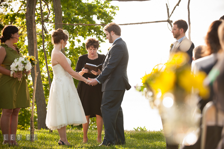 Bride, Groom and officiant under open wooden canopy. Kent Island Maryland Matapeake Beach wedding ceremony and getting ready photo, by wedding photographers of Leo Dj Photography. http://leodjphoto.com