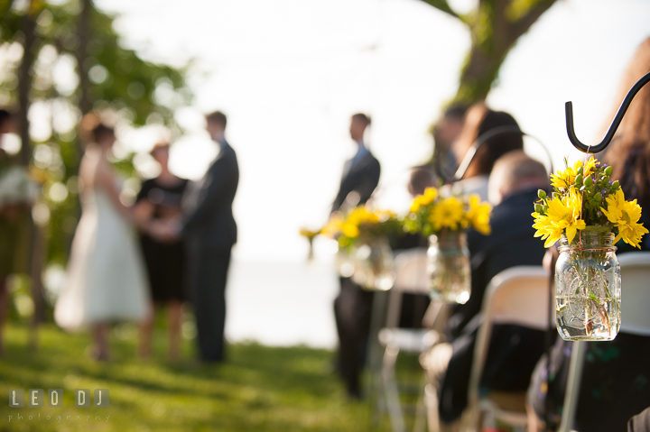 Flower decorations on the isle with Bride and Groom in the background. Kent Island Maryland Matapeake Beach wedding ceremony and getting ready photo, by wedding photographers of Leo Dj Photography. http://leodjphoto.com