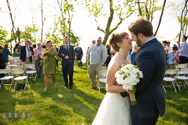 Bride and Groom smiled and almost kissed as they walk out of the isle. Kent Island Maryland Matapeake Beach wedding ceremony and getting ready photo, by wedding photographers of Leo Dj Photography. http://leodjphoto.com
