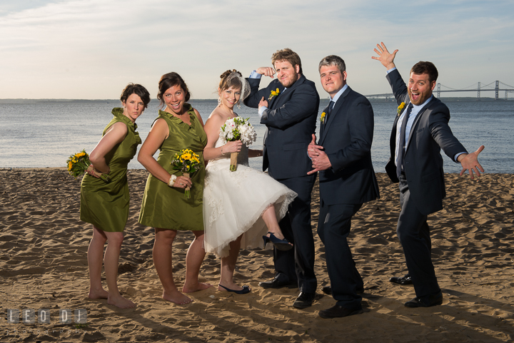 Wedding party of Bride, Groom, Bridesmaid, Maid of honor, Best Man and Groomsman goofy posing on the beach with Bay Bridge in the background. Kent Island Maryland Matapeake Beach wedding reception party and romantic session photo, by wedding photographers of Leo Dj Photography. http://leodjphoto.com