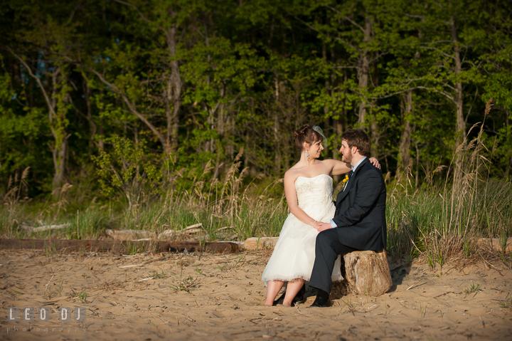 Bride sitting on Groom's lap on the beach. Kent Island Maryland Matapeake Beach wedding reception party and romantic session photo, by wedding photographers of Leo Dj Photography. http://leodjphoto.com