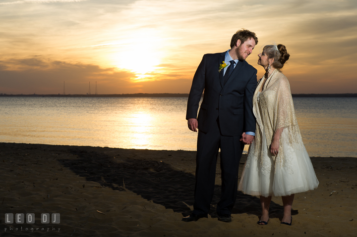 Bride and Groom on beach smiling at each other with sunset in the background. Kent Island Maryland Matapeake Beach wedding reception party and romantic session photo, by wedding photographers of Leo Dj Photography. http://leodjphoto.com