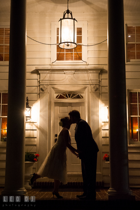 Silhouette of Bride and Groom kissing on the front porch of the building at the venue. Kent Island Maryland Matapeake Beach wedding reception party and romantic session photo, by wedding photographers of Leo Dj Photography. http://leodjphoto.com