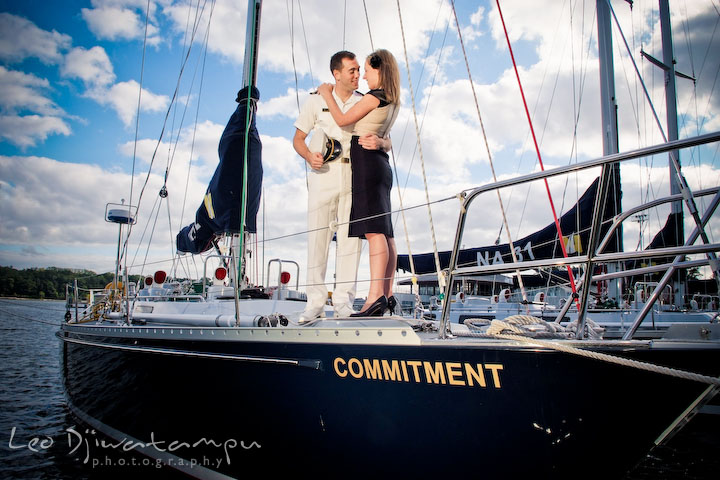 Engaged couple standing on sail boat hugging. Pre-wedding engagement photo session USNA US Naval Academy with Navy boat, uniform, vintage clothing, and vintage car