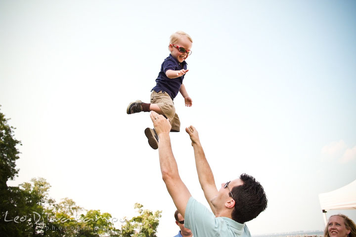 Father playing and throwing up his toddler son up in the air. Cove Creek Country Club, Stevensville, Kent Island, Eastern Shore, Maryland Wedding Photographer, beach wedding photographer