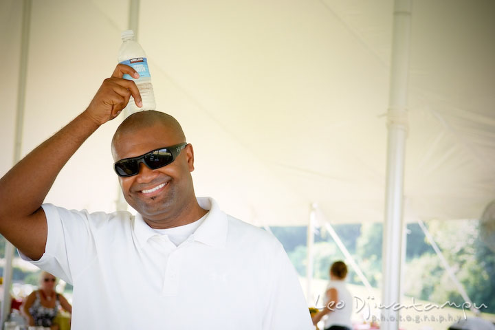 Guest putting cold water bottle on his head. Cove Creek Country Club, Stevensville, Kent Island, Eastern Shore, Maryland Wedding Photographer, beach wedding photographer