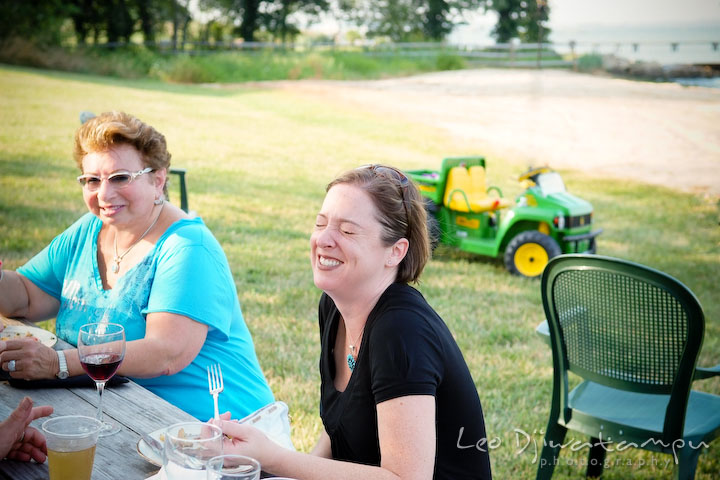 Guests sitting on an outdoor picnic bench, laughing. Cove Creek Country Club, Stevensville, Kent Island, Eastern Shore, Maryland Wedding Photographer, beach wedding photographer
