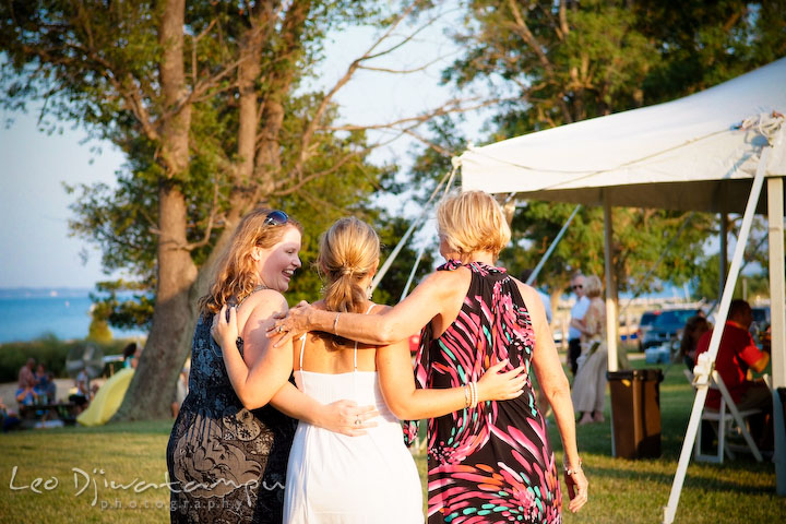 Bride, sister and mother holding each other walking to tent. Cove Creek Country Club, Stevensville, Kent Island, Eastern Shore, Maryland Wedding Photographer, beach wedding photographer