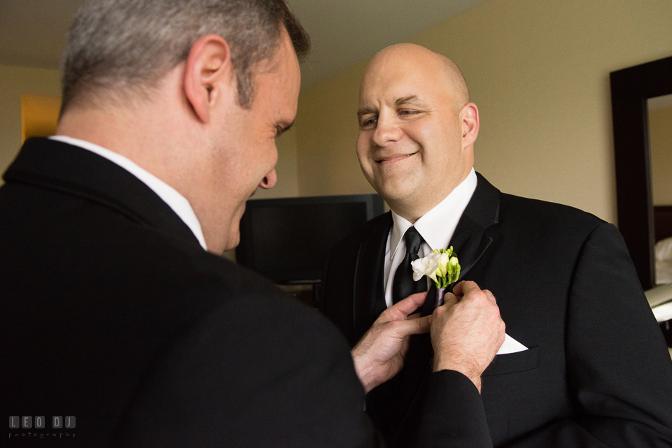 Westin Annapolis Hotel best man put boutonniere on groom photo by Leo Dj Photography