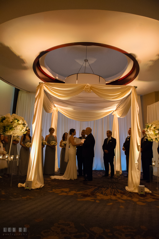 Westin Annapolis Hotel bride and groom reading vows during ceremony under canopy photo by Leo Dj Photography