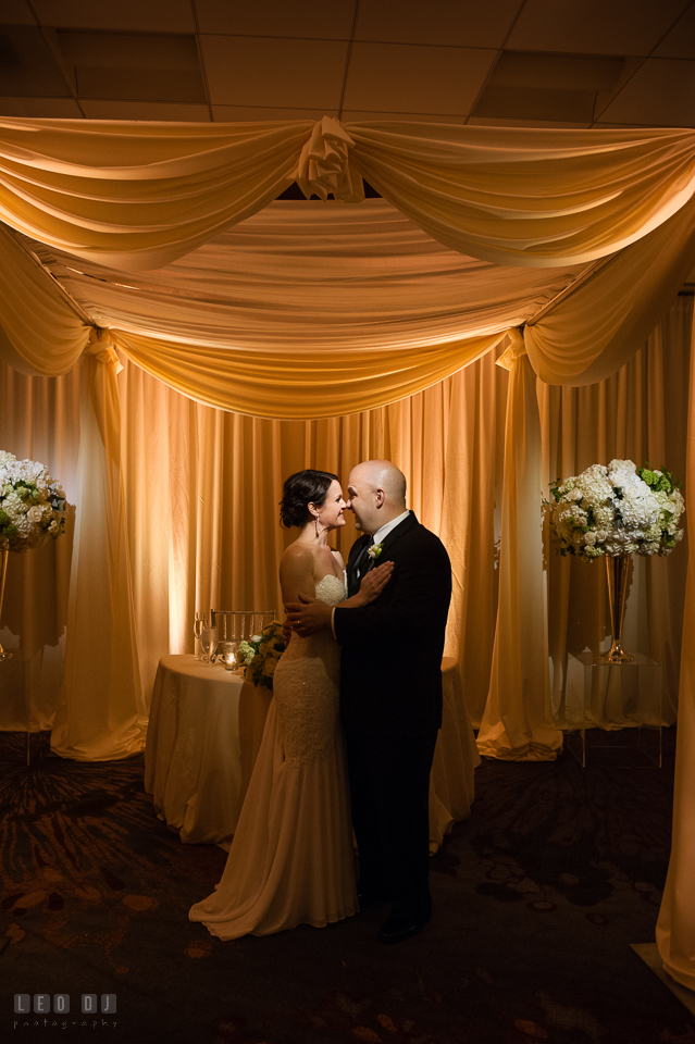 Westin Annapolis Hotel bride and groom hugging by sweetheart table under canopy photo by Leo Dj Photography