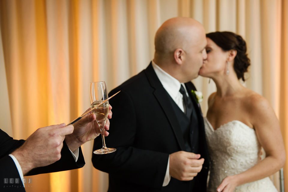 Westin Annapolis Hotel bride and groom kissing while guests clinking glasses photo by Leo Dj Photography