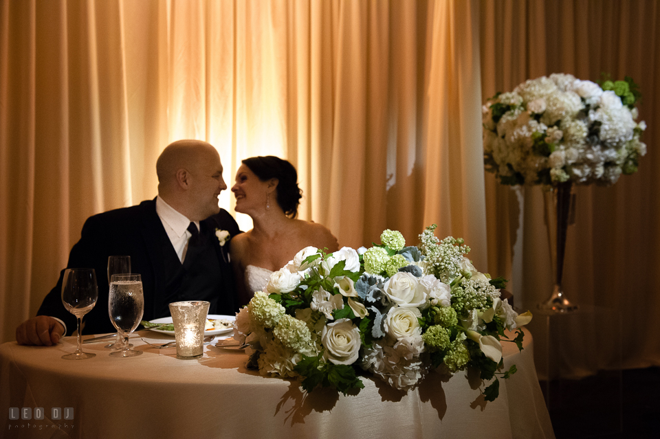 Westin Annapolis Hotel bride and almost kissed by sweetheart table with flowers from Blue Vanda Designs photo by Leo Dj Photography