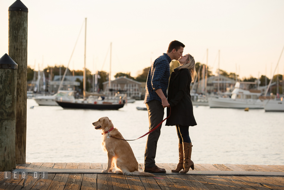 Downtown Annapolis Maryland engaged couple with their dog at dock almost kissing engagement photo by Leo Dj Photography.