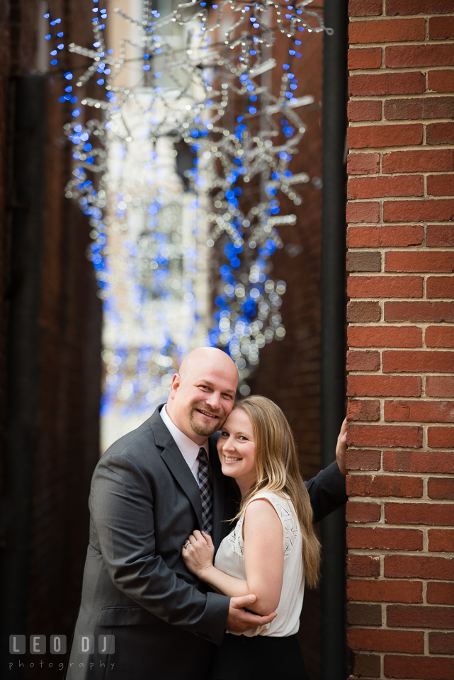 Downtown Annapolis Maryland engaged girl cuddling with fiance in alley with Christmas lights photo by Leo Dj Photography.