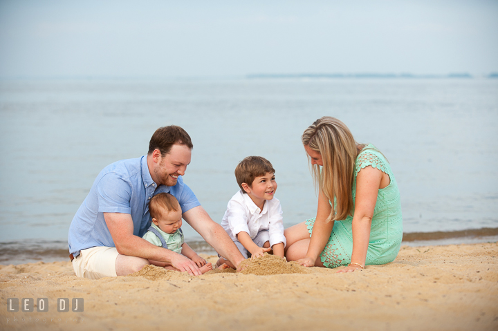 Happy family playing beach sand together. Chesapeake Bay, Kent Island, Annapolis, Eastern Shore Maryland children and family lifestyle portrait photo session by photographers of Leo Dj Photography. http://leodjphoto.com