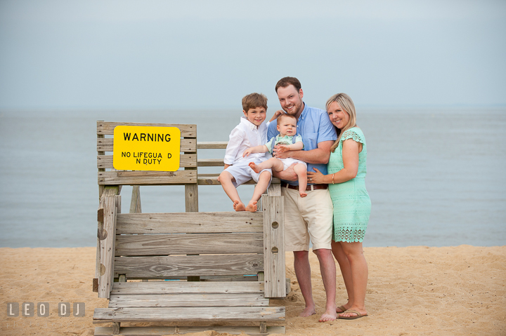 A family of four posing by a lifeguard post chair. Chesapeake Bay, Kent Island, Annapolis, Eastern Shore Maryland children and family lifestyle portrait photo session by photographers of Leo Dj Photography. http://leodjphoto.com