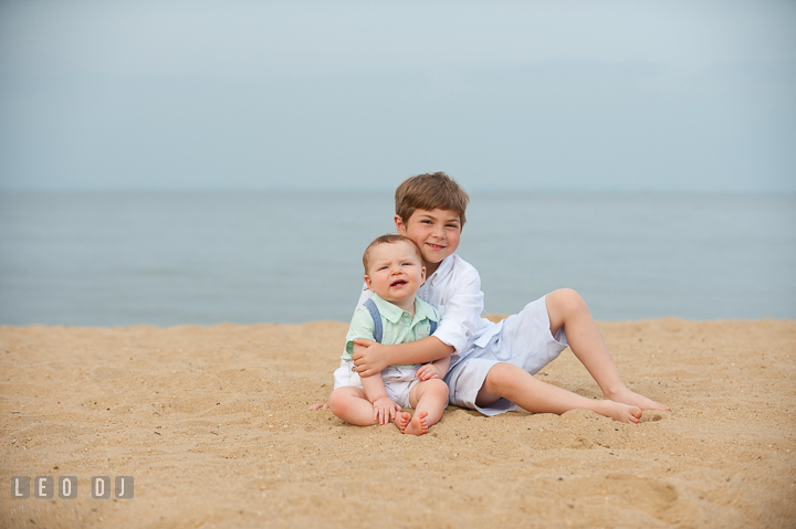 Big brother giving hug to little baby brother. Chesapeake Bay, Kent Island, Annapolis, Eastern Shore Maryland children and family lifestyle portrait photo session by photographers of Leo Dj Photography. http://leodjphoto.com