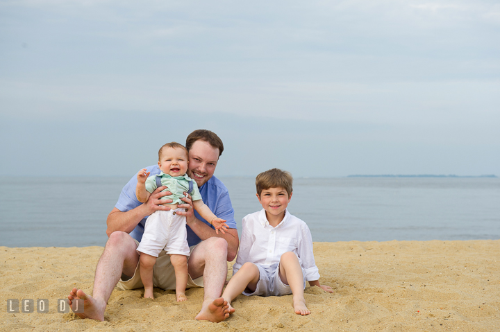 Father, son, and baby boy posing together on the beach. Chesapeake Bay, Kent Island, Annapolis, Eastern Shore Maryland children and family lifestyle portrait photo session by photographers of Leo Dj Photography. http://leodjphoto.com