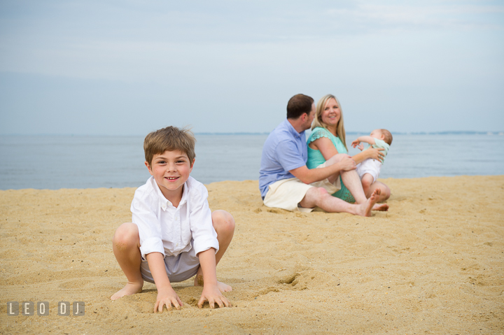 Boy smiling while Father, Mother and baby brother playing together in the background. Chesapeake Bay, Kent Island, Annapolis, Eastern Shore Maryland children and family lifestyle portrait photo session by photographers of Leo Dj Photography. http://leodjphoto.com