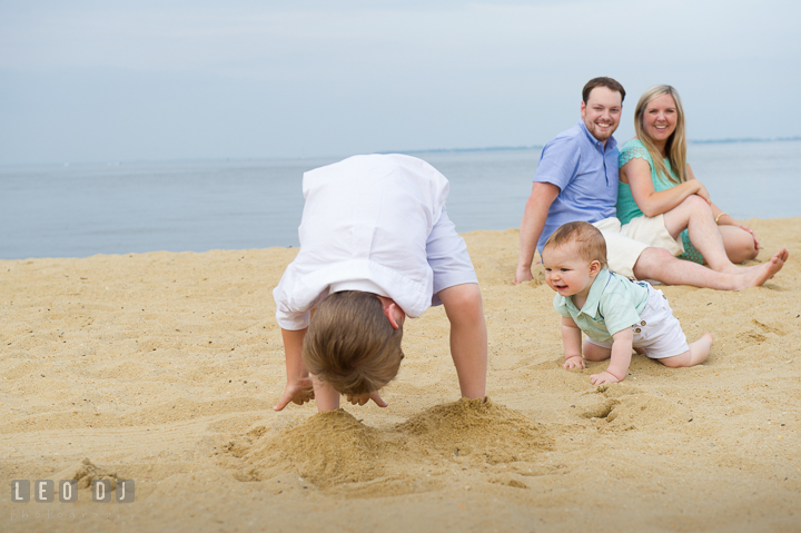 Big brother playing peek-a-boo with baby brother. Chesapeake Bay, Kent Island, Annapolis, Eastern Shore Maryland children and family lifestyle portrait photo session by photographers of Leo Dj Photography. http://leodjphoto.com