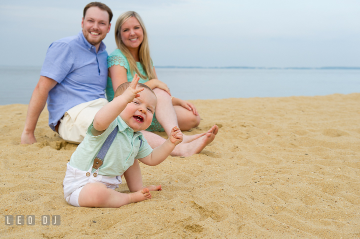 Baby boy trying to talk to photographer while Father and Mother smiling in the background. Chesapeake Bay, Kent Island, Annapolis, Eastern Shore Maryland children and family lifestyle portrait photo session by photographers of Leo Dj Photography. http://leodjphoto.com