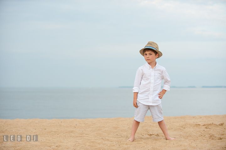 Boy standing on beach sand posing with straw hat. Chesapeake Bay, Kent Island, Annapolis, Eastern Shore Maryland children and family lifestyle portrait photo session by photographers of Leo Dj Photography. http://leodjphoto.com