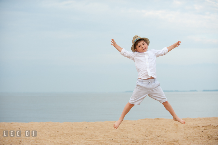 Little boy at the beach jumping high up in the air. Chesapeake Bay, Kent Island, Annapolis, Eastern Shore Maryland children and family lifestyle portrait photo session by photographers of Leo Dj Photography. http://leodjphoto.com