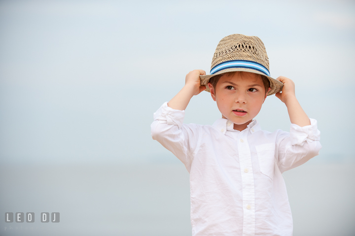 Young boy posing and holding his fedora hat. Chesapeake Bay, Kent Island, Annapolis, Eastern Shore Maryland children and family lifestyle portrait photo session by photographers of Leo Dj Photography. http://leodjphoto.com